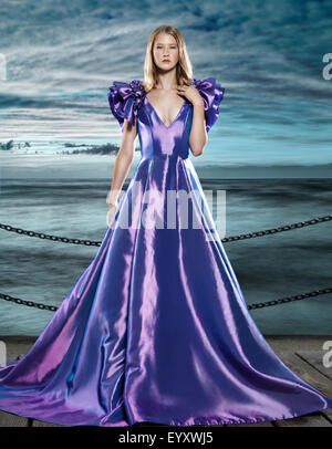 Young blond woman wearing a beautiful long blue dress, evening gown, at waterfront, artistic fashion portrait - Stock Photo