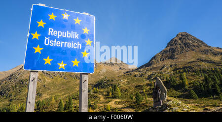country sign in front of memorial and mountain scenery, Austria - Stock Photo