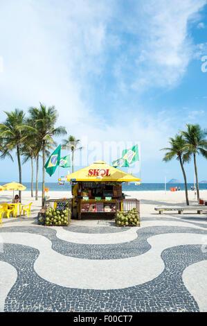RIO DE JANEIRO, BRAZIL - MARCH 27, 2015: Traditional beachside kiosk with Brazilian flags and palm trees on Copacabana - Stock Photo