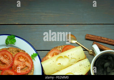 Cheese and tomato sandwich with a cup of coffee on top of a wooden table with copy space - Stock Photo