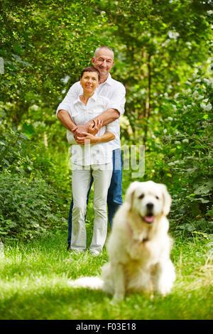 Senior couple with golden retriever dog as a pet in their garden - Stock Photo
