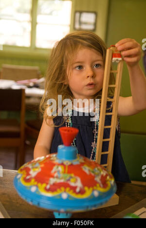 3 year old girl engrossed in playing with traditional wooden toys at a heritage event, Rural Life Centre, Tilford, - Stock Photo