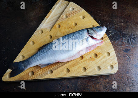 uncoucked fish on an old brown table - Stock Photo