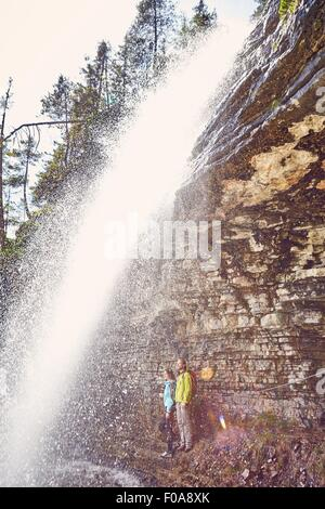 Young couple standing underneath waterfall, looking out,  Tyrol, Austria - Stock Photo