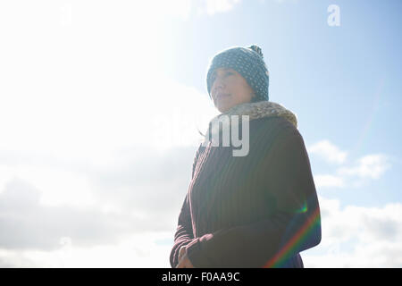Portrait of mature woman wearing knit hat against blue sky - Stock Photo