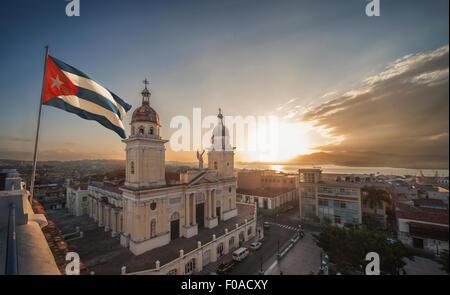 Cuban flag over Plaza de la catedral at sunset, Santiago de Cuba, Cuba - Stock Photo