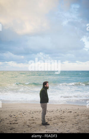Mid adult man on stormy beach, Sorso, Sassari, Sardinia, Italy - Stock Photo