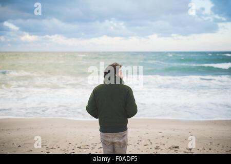 Rear view of man looking sideways on windy beach, Sorso, Sassari, Sardinia, Italy - Stock Photo