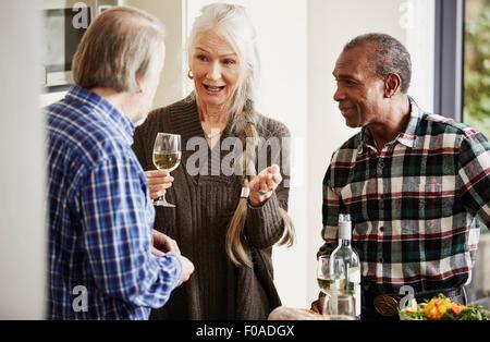 Senior friends talking in kitchen with wine - Stock Photo