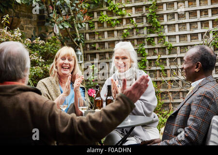 Senior friends sitting in garden talking - Stock Photo