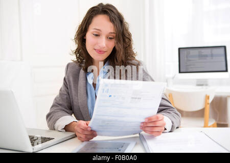 view of a Young attractive woman doing paperwork - Stock Photo