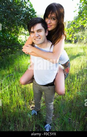 Young man giving girlfriend piggyback ride in park - Stock Photo