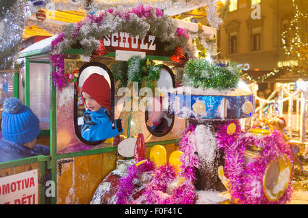 Child on a toy train at a Funfair at a Christmas market in Brno, Czech Republic - Stock Photo