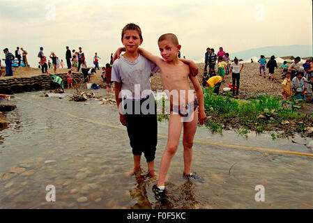 Kosovan refugees at camp Strankovic Macedonia 1999 , to young boys play in the stream that runs through the camp - Stock Photo