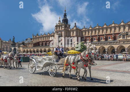 Horse-drawn carriages await tourists on the Krakow Cloth Hall, of the Main Market Square, Poland, Lesser Poland, - Stock Photo