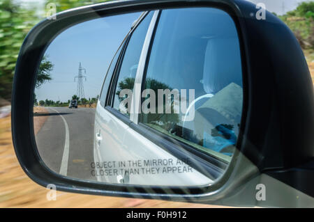 View through rear-view mirror of a car moving on highway through desert in high speed with surrounding motion blurred - Stock Photo