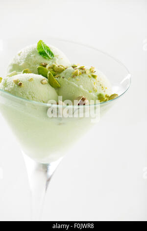 A scoop of pistachio ice cream with pistachios in glass close up. - Stock Photo