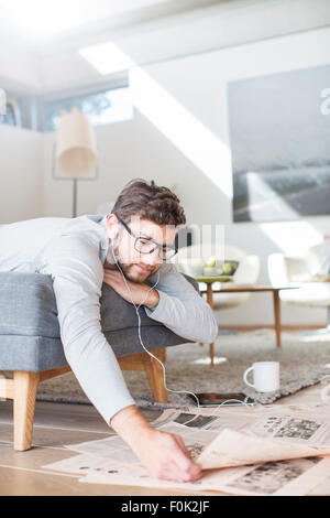Man with headphones reading newspaper and drinking coffee in living room - Stock Photo