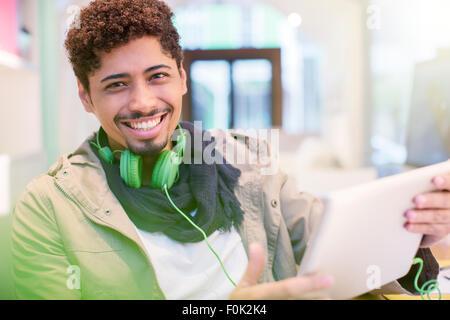 Portrait creative businessman with headphones using digital tablet - Stock Photo