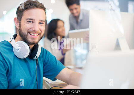Portrait confident creative businessman with headphones working in office - Stock Photo
