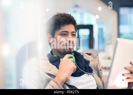 Creative businessman with headphones using digital tablet - Stock Photo