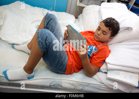 Young boy lying on his bed looking at his tablet alone. - Stock Photo