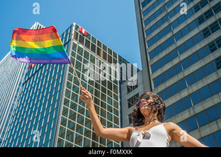 MONTREAL, CANADA, 16th August 2015. A female spectator is waving the gay rainbow flag at the 2015 Gay Pride Parade - Stock Photo