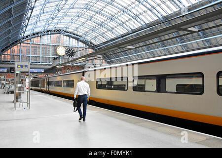 Departing lone traveller makes his way along St Pancras International Station platform to his reserved Eurostar - Stock Photo