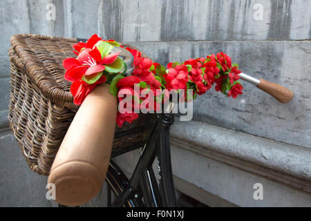 Detail of a bike with flowers decorating the front in Bruges, Belgium - Stock Photo