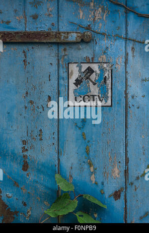 CCTV warning sign pictogram on faded old door. - Stock Photo