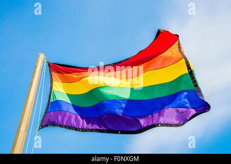 Gay rainbow flag over blue sky - Stock Photo