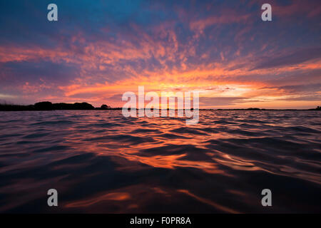 Sunset Explosion viewed from the water line on the Gulf of Mexico - Stock Photo