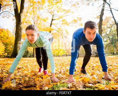 Young couple in starting position prepared for running in autumn nature - Stock Photo