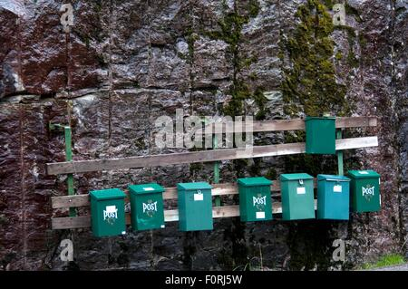 green mailboxes on stone wall - Stock Photo