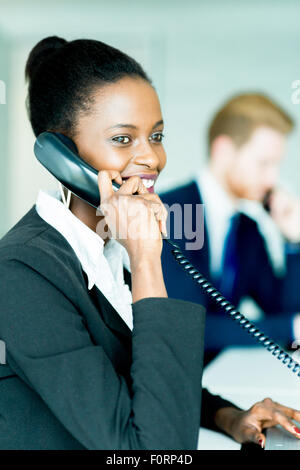 A beautiful, black, young woman working at a call center in an office with her red haird partner on the other end - Stock Photo
