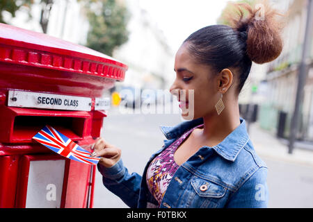 young woman posting a postcard in London - Stock Photo