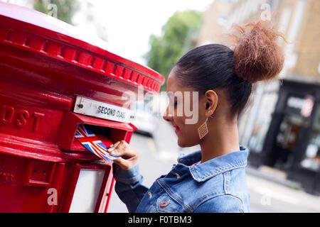 young woman sending a postcard in England - Stock Photo