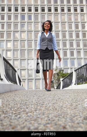 Low angle front view of business woman walking, carrying briefcase, smiling, looking away - Stock Photo