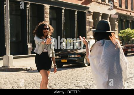 Two mid adult female friends greeting each other on city street - Stock Photo