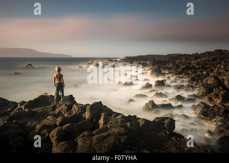 Boy on edge of cliff, Madalena, Pico, Azores, Portugal - Stock Photo