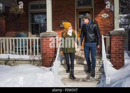 Couple leaving house in winter - Stock Photo