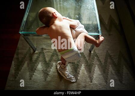 Boy half-climbing up on glass table - Stock Photo