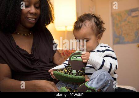 Mid adult woman and curious toddler daughter with baby boot - Stock Photo