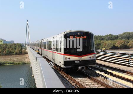 Vienna Subway train on U2 line to Seestadt approaching Donaustadtbrucke station coming off the railway bridge over - Stock Photo