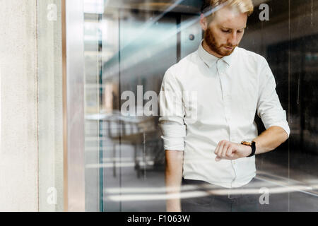 Businessman checking watch while standing in glass covered elevator - Stock Photo
