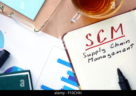 Notepad with word SCM supply chain management concept and marker. - Stock Photo