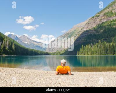 Hiker laying near mountain lake, Glacier National Park, Montana, United States - Stock Photo