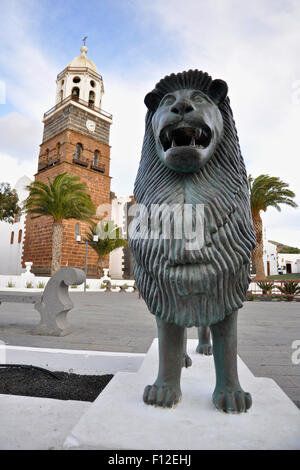 Lion sculpture near the tower of the Nuestra Señora de Guadalupe Church at Teguise, Lanzarote (Canary Islands, Spain) - Stock Photo