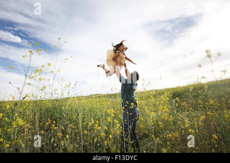 Father lifting daughter in the air - Stock Photo