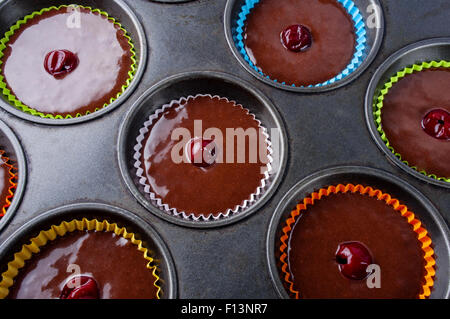 Raw chocolate muffin pastry dough with cherry ready for baking. - Stock Photo
